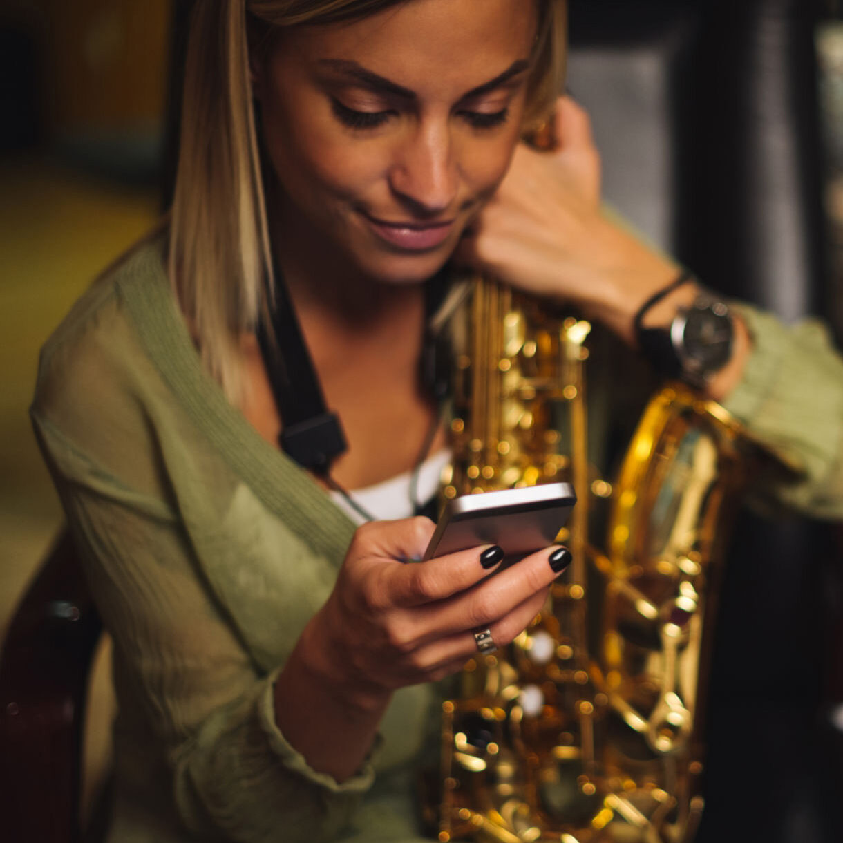 Young female musician checking her phone while practicing in a music studio.